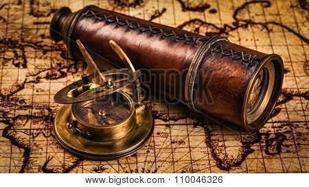 Travel geography navigation concept background - panorama of old vintage retro compass with sundial and spyglass on ancient world map