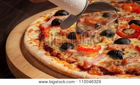 Panorama of pizza cutter (wheel) slicing ham pizza with capsicum and olives on wooden board on table