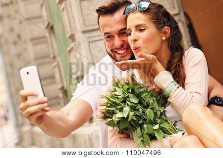A picture of a young romantic couple using smartphone in the city