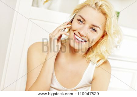 A picture of a young woman talking on the phone at home