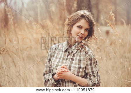 Adorable young woman in plaid shirt on cozy country walk on field
