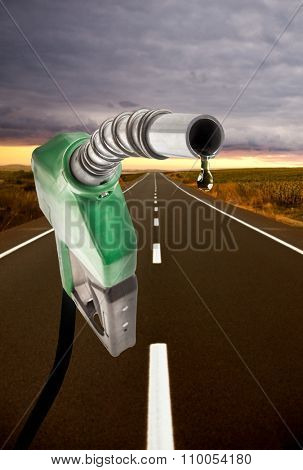 Green gas pump with one last drop and the road on the background