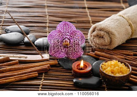 Spa setting on mat with pink orchid