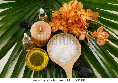 Spa set with orchid ,spa oil , salt in spoon, candle on palm leaf