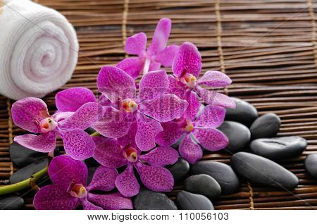 Lying on purple orchid with stones on bamboo mat