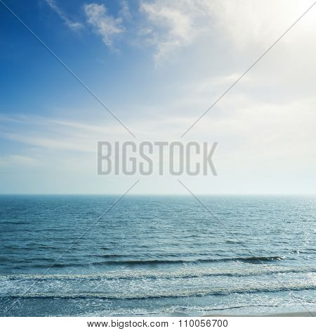 sun in clouds over sea with waves