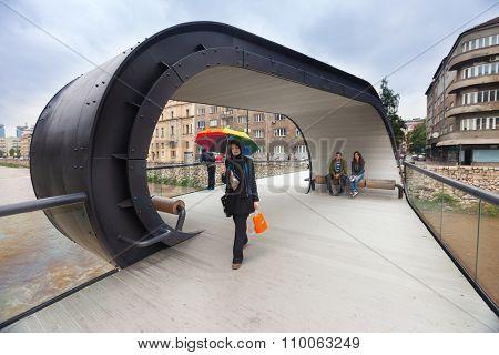 SARAJEVO, BOSNIA AND HERZEGOVINA: JUNE 19, 2014: Muslim woman with colourful umbrella on Festina lente, pedestrian bridge over Miljacka river.