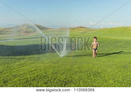 Happy summer vacation for kids on green meadow splash sprinkle water