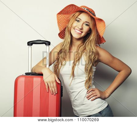Portrait of  young woman wearing big straw orange hat  standing with orange travel bag
