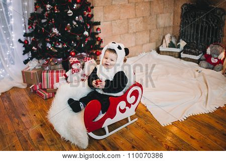 little boy smiling next to the Christmas tree , blurred