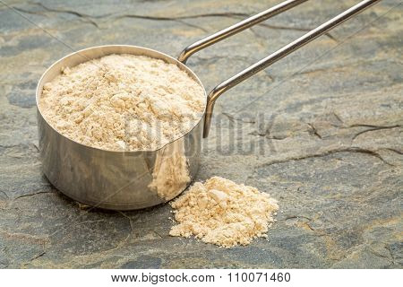 maca root powder on a metal measuring scoop against slate stone