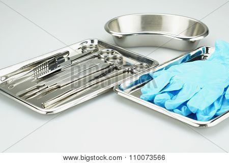 Medical Instruments And Blue Gloves In A Stainless Steel Tray