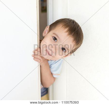 Kid peeking out of the open room door