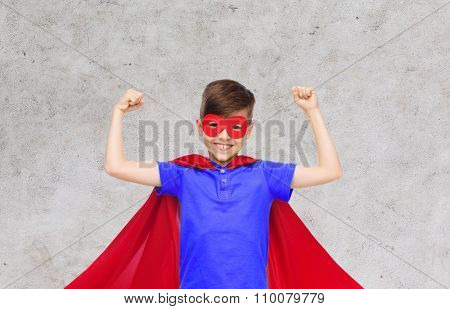 carnival, childhood, power, gesture and people concept - happy boy in red super hero cape and mask showing fists over gray background