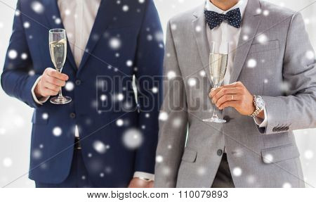 people, celebration, homosexuality, same-sex marriage and love concept - close up of happy married male gay couple in suits drinking sparkling wine from glasses on wedding over snow effect