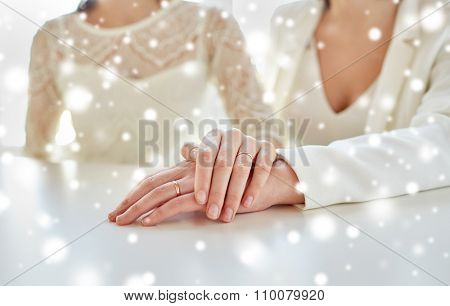 people, homosexuality, same-sex marriage and love concept - close up of lesbian couple hands with wedding rings over snow effect