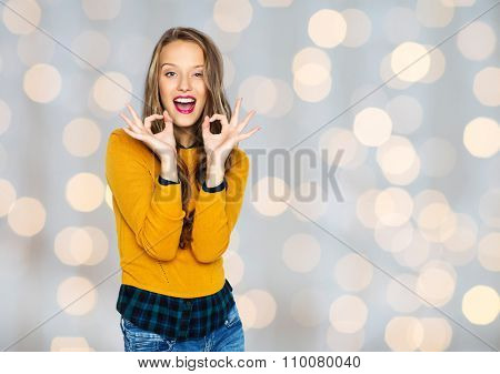 people, gesture, style and fashion concept - happy young woman or teen girl in casual clothes showing ok hand sign over holidays lights background