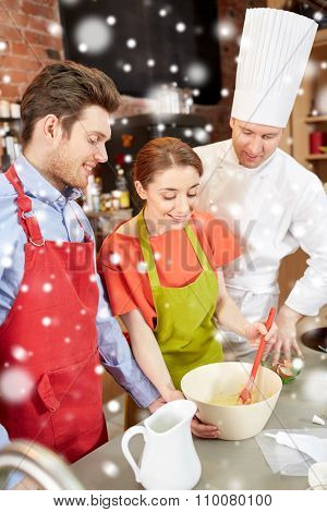 cooking class, bakery, cooking food and people concept - happy couple and male chef cook prepearing cream or dough in kitchen over snow effect