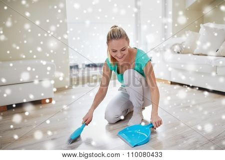 people, housework and housekeeping concept - happy woman with brush and dustpan floor at home over snow effect