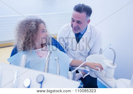 Pediatric dentist smiling to his patient at the dental clinic