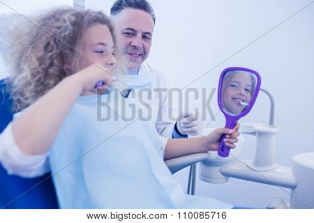 Pediatric dentist teaching girl how to brush teeth at the dental clinic