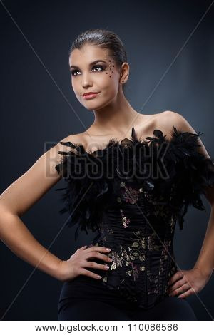 Attractive woman posing in black party dress with boa, luxury makeup, smiling.