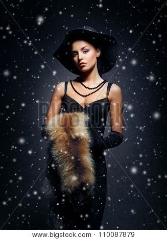 Young, rich and beautiful woman over the vintage winter background with snowflakes.