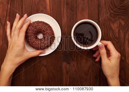 close-up photo of brown table with chocolate donut on white plate and womans hand holding cup of coffee