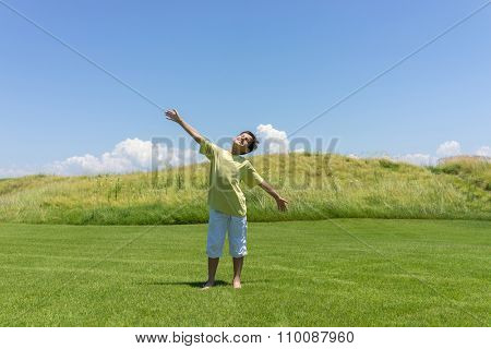 Boy with open hands in beautiful nature