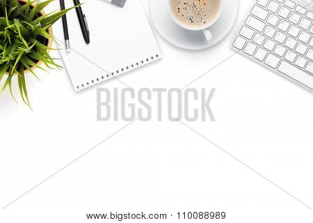 Office desk table with computer, supplies, coffee cup and flower. Isolated on white background. Top view with copy space