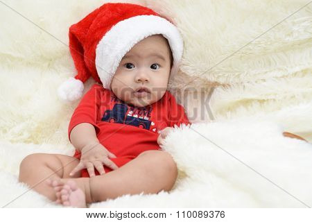 Asian Cute Baby Sitting On A Soft Cloth In The Living Room. Baby With Santa Hat