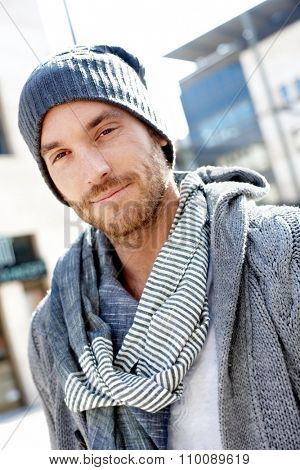 Outdoor portrait of goodlooking stylish guy standing, wearing scarf and smiling at camera.
