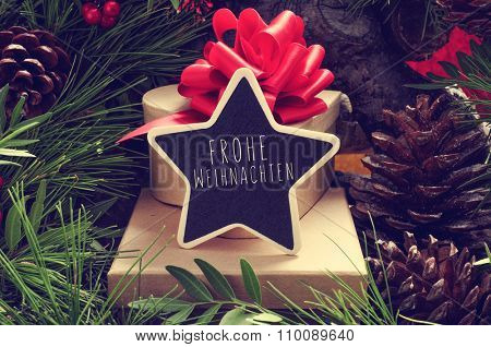 a star-shaped chalkboard with the text Frohe Weihnachten, Merry Christmas in german, on a pile of gifts placed under the christmas tree and surrounded by natural ornaments such as pine cones