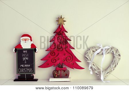 a chalkboard in the shape of santa claus with the text we wish you a merry christmas, a rustic wooden christmas tree and a rustic heart-shaped ornament on a white surface against a white background