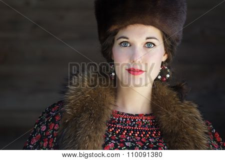 Head And Shoulders Portrait Of Russian Beauty With Blue Eyes Wearing Fur Cossack Hat