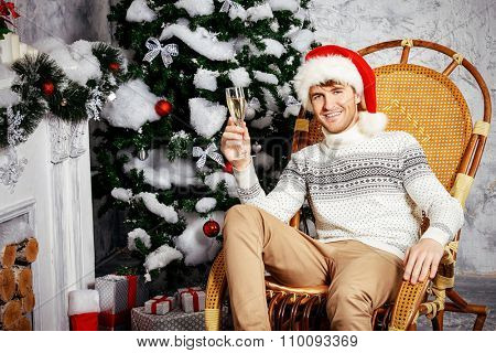 Happy young man with a glass of champagne celebrating winter holidays at home beautifully decorated for Christmas.