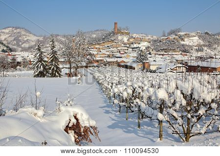 Rural field and small town on background covered with snow under blue sky in Piedmont, Northern Italy.