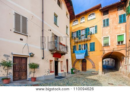 Small backstreet among between colorful houses in town of Saluzzo in Piedmont, Northern Italy.