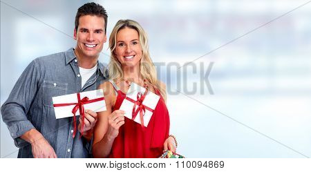 Couple with  envelope Christmas gift over blue background.