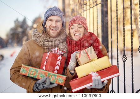 Young ecstatic couple with gift-boxes looking at camera outdoors
