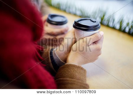 Human hands holding drink in plastic glass