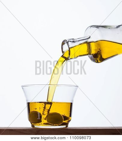 Pouring Olive Oil From A Bottle Into A Glass