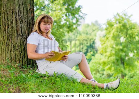 Mature Woman Of 50 Years Old Reading A Book On The Lawn In The Park