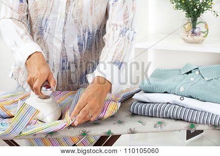 Woman ironing shirts