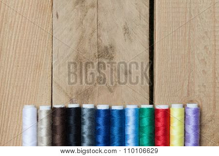 Colorful Thread Spools On Wooden Background