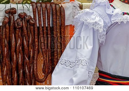 Romanian Traditional Sausages Hanging On A Fence. Specific Costumes.