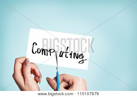Woman hands cutting card with the word computing