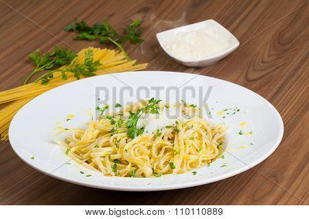 Spaghetti Aglio e Olio, an Italian recipe of pasta, in a wooden table.