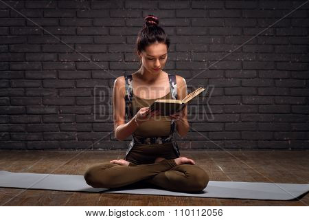 Beautiful Girl Doing Yoga Exercises And Read Book