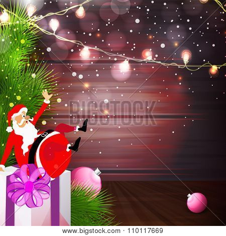 Funny Santa Claus on big gift box with ornaments on shiny lights decorated elegant background for Merry Christmas celebration.
